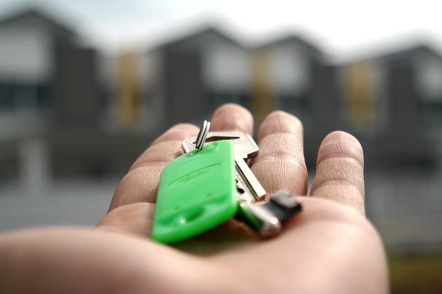 Person holding key to house